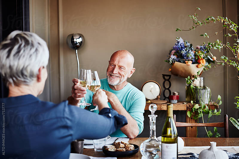 Senior Couple Toasting Wine Glasses At Dining Table by ALTO IMAGES for Stocksy United