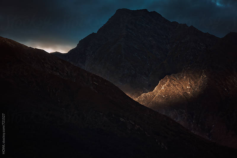 Morning light breaks on the rough peaks of a mountain by HOWL for Stocksy United