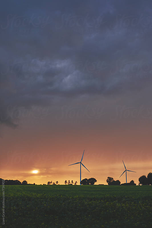 Wind turbines against a dark stormy sky at sunset. Norfolk, UK. by Liam Grant for Stocksy United
