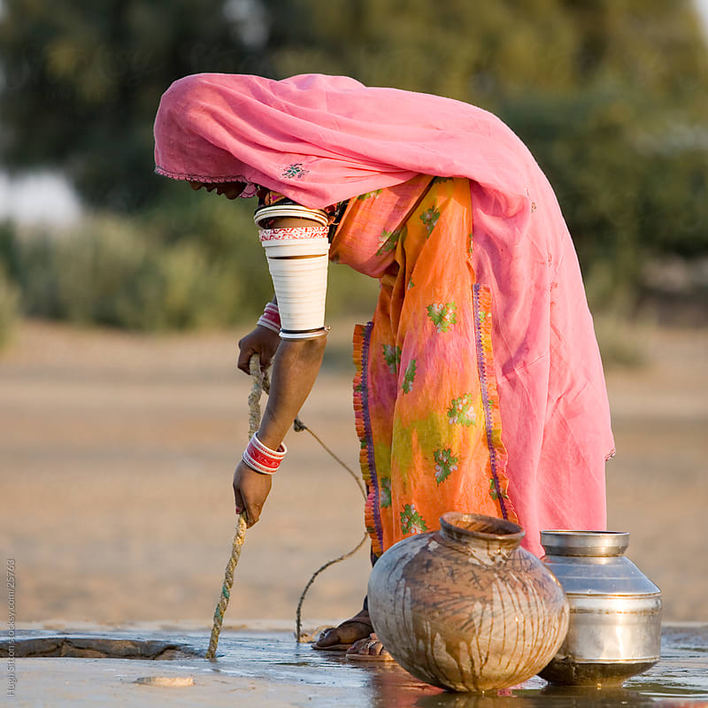 Indian woman wearing sari pulling water from well in desert.  by Hugh Sitton for Stocksy United