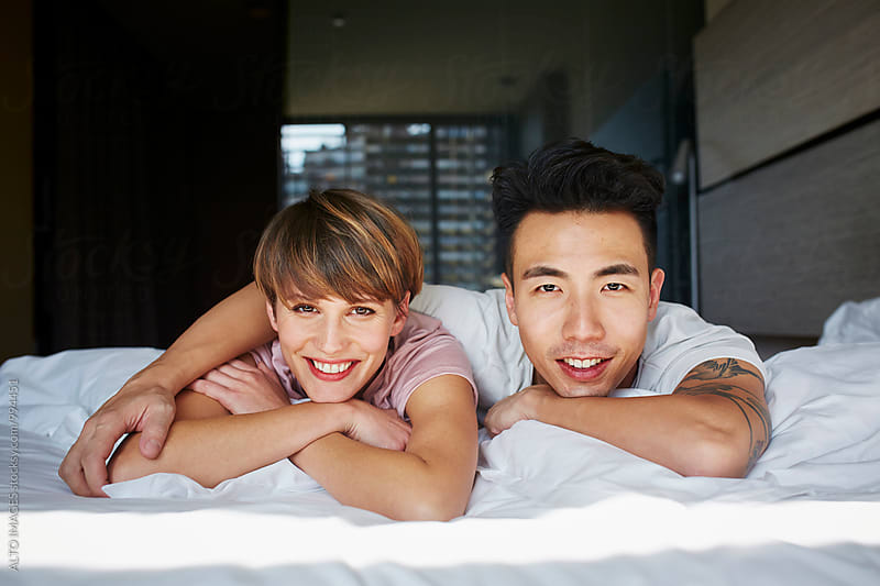 Portrait Of Happy Couple Lying In Bed by ALTO IMAGES for Stocksy United