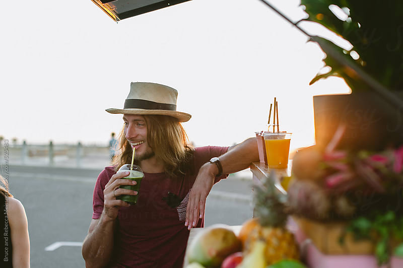 Man with fresh juice by Bruce and Rebecca Meissner for Stocksy United