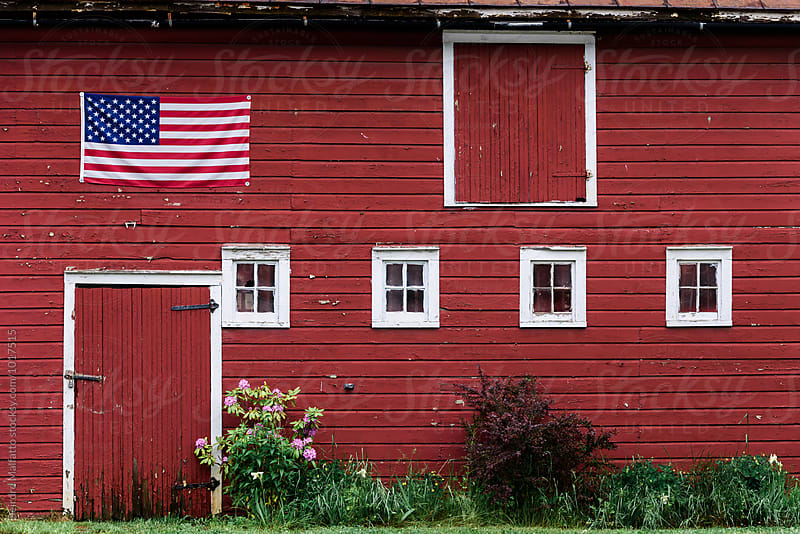 side of an old red barn with american flag,  by Deirdre Malfatto for Stocksy United