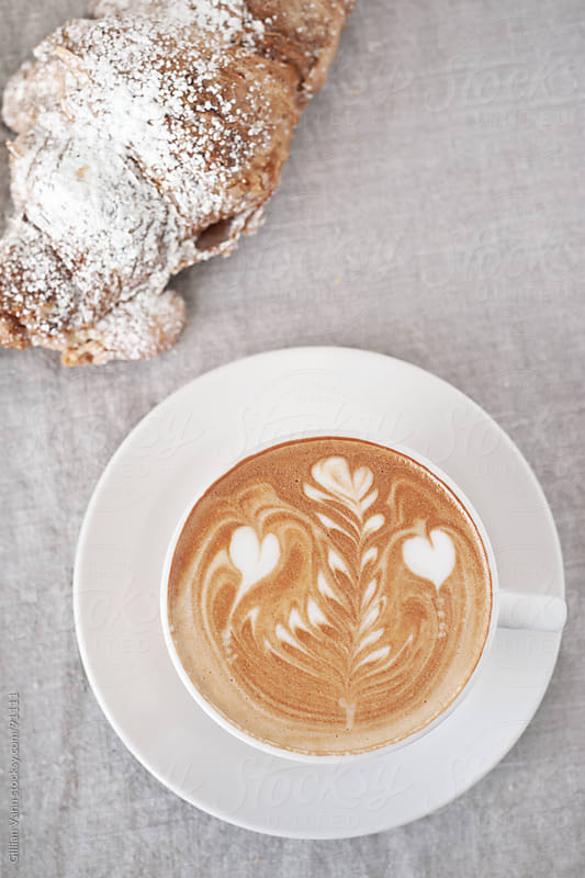 coffee with almond croissant by Gillian Vann for Stocksy United