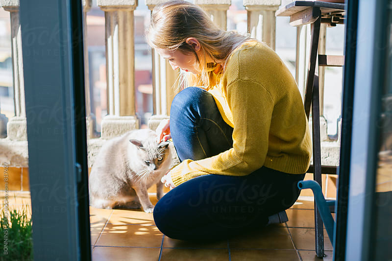 Side view of a woman with her siamese cat enjoying a sunny day outside. by BONNINSTUDIO for Stocksy United