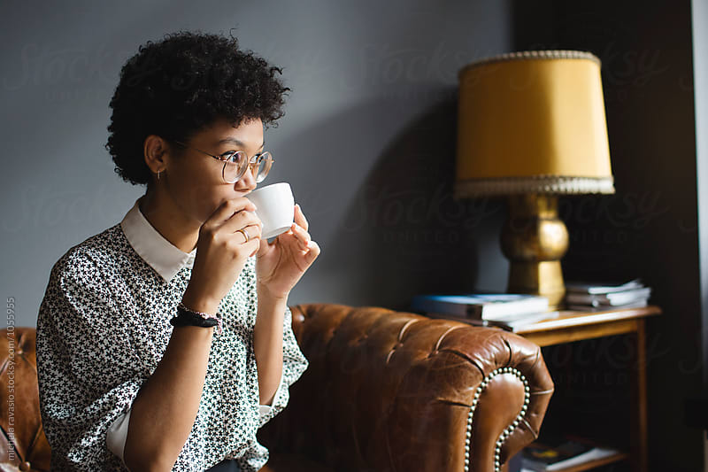 Afro woman drinking a cup of coffee by michela ravasio for Stocksy United