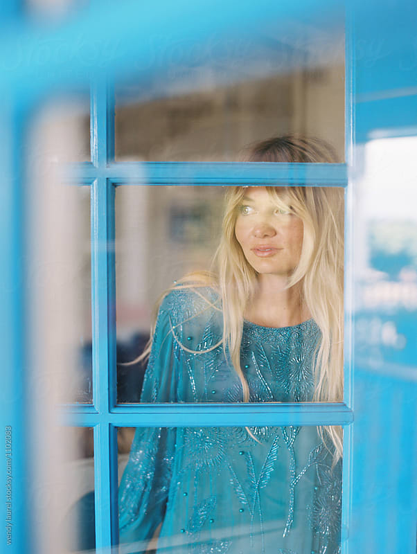 blonde girl looking out through door by wendy laurel for Stocksy United
