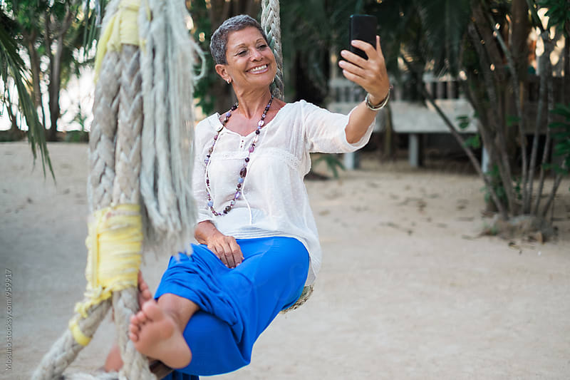 Senior Woman Taking Selfie on a Beach Swing by Mosuno for Stocksy United