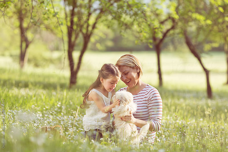 Mother and daughter playing with their pet by Dejan Ristovski for Stocksy United