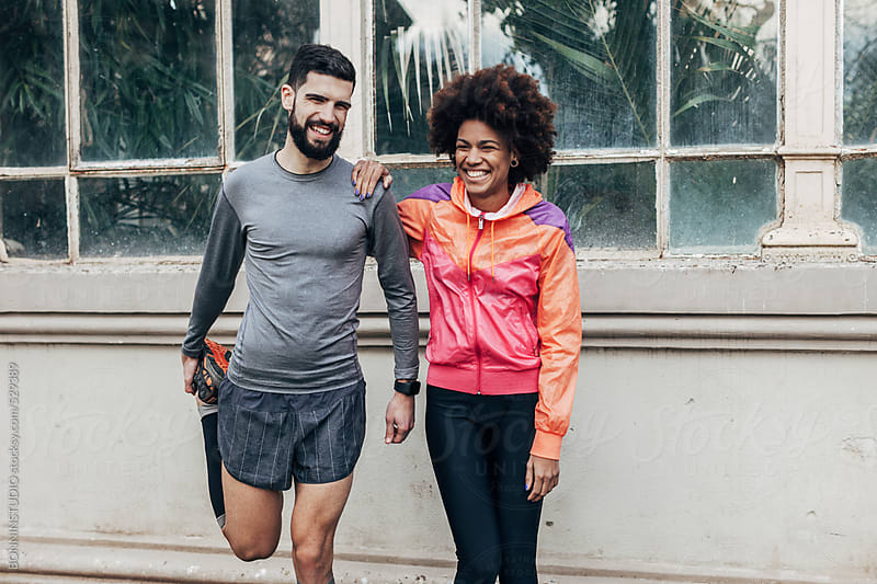 Smiling multiethnic runners doing stretching exercises in the park. by BONNINSTUDIO for Stocksy United