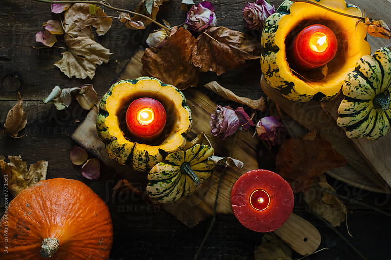 Autumn still life: pumpkins,candles and dried flowers with autumn leaves on table. by Darren Muir for Stocksy United