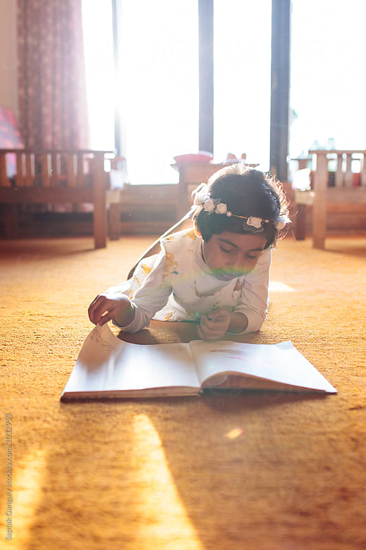 Little girl reads a book lying on the floor by Saptak Ganguly for Stocksy United