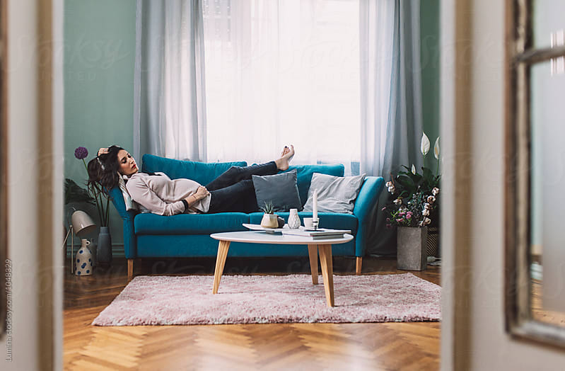 Pregnant Woman Lying on a Couch by Lumina for Stocksy United