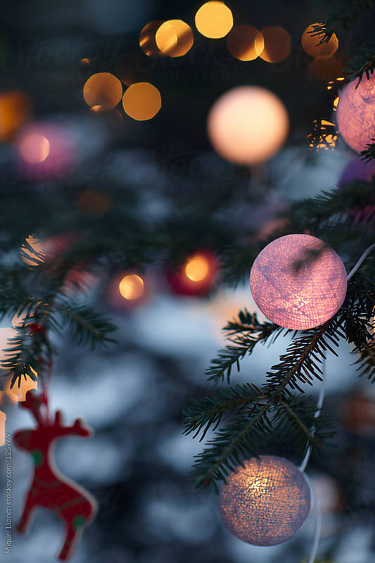 Christmas tree, lit balls and ornaments at night by Miquel Llonch for Stocksy United