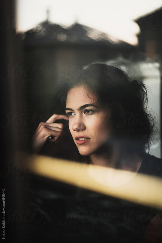 Portraits of a beautiful young woman by the window by Natasa Kukic for Stocksy United