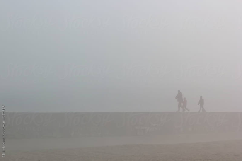 People walking on a dyke on a foggy day by Melanie Kintz for Stocksy United