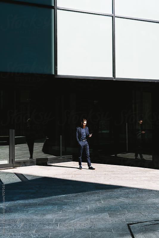 Businessman walking in the corporate area by GIC for Stocksy United