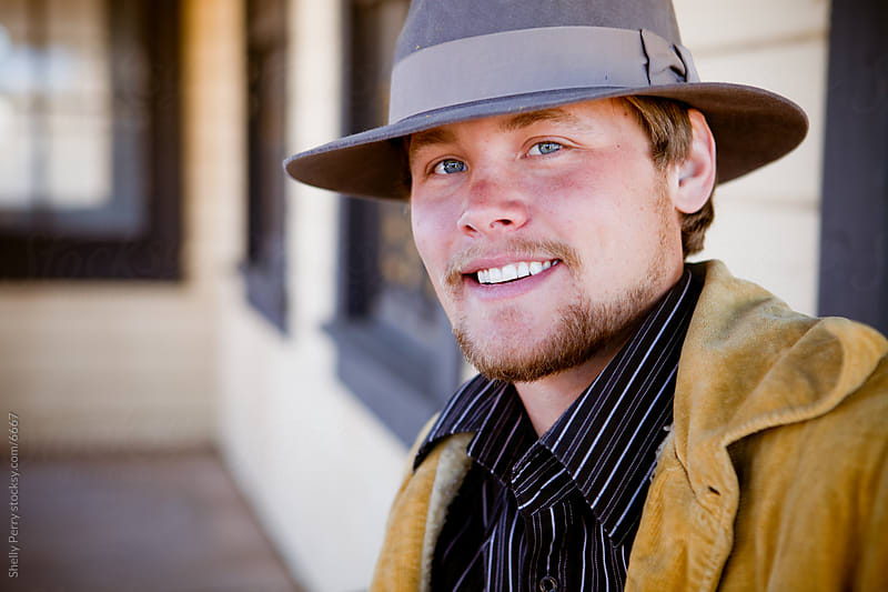 A cute Cowboy portrait; young man with fantastic smile and blue eyes by Shelly Perry for Stocksy United
