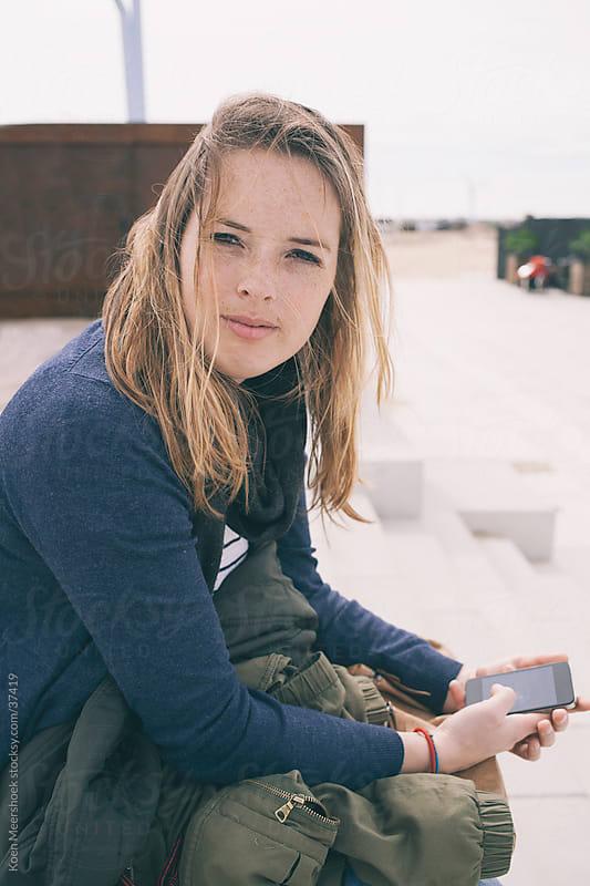 Girl holding her phone while sitting in the sun by Koen Meershoek for Stocksy United