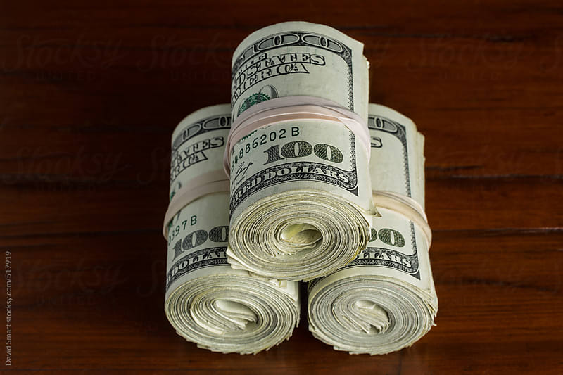 Three rolls of US one hundred dollar bills by David Smart for Stocksy United
