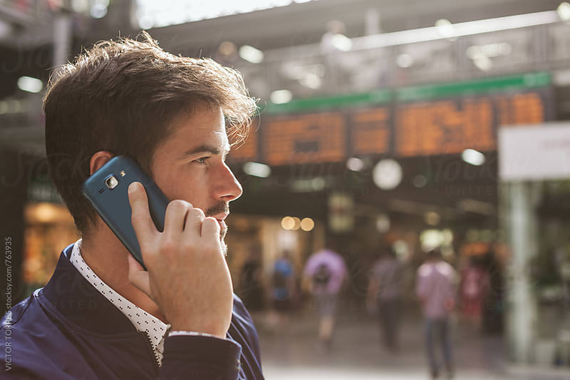 Elegant Young Businessman Talking by Phone with the Flights Timetable Behind Him by VICTOR TORRES for Stocksy United