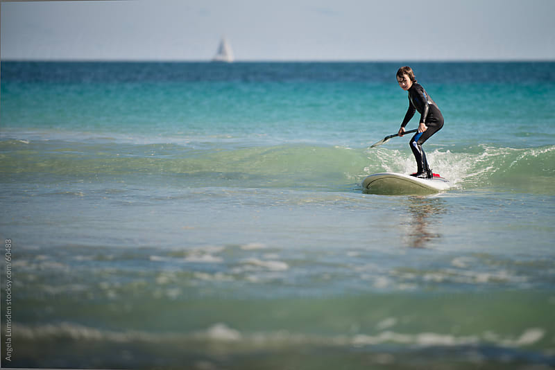 Young boy catching a wave on a stand up paddle board by Angela Lumsden for Stocksy United