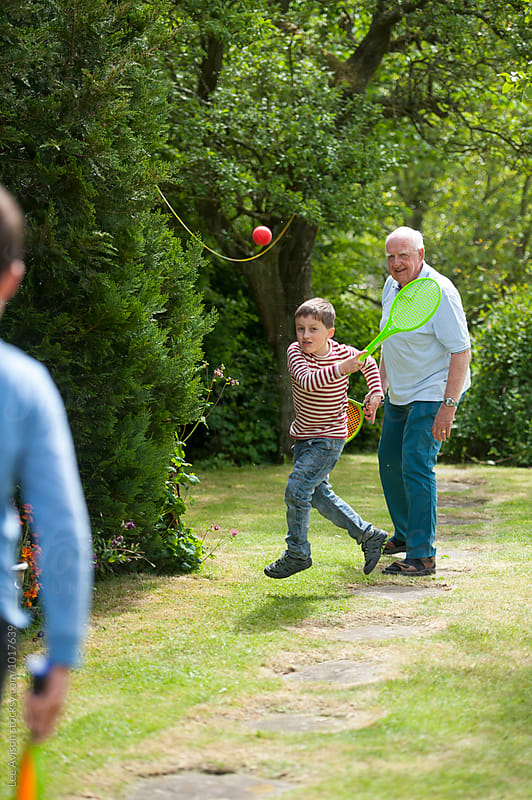 grandfather and grandsons playing tennis together by Lee Avison for Stocksy United