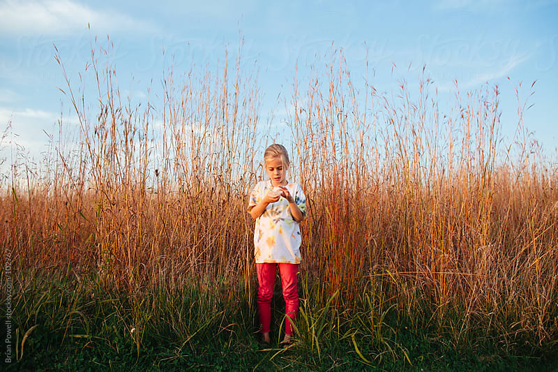 girl exploring nature in tall grass by Brian Powell for Stocksy United
