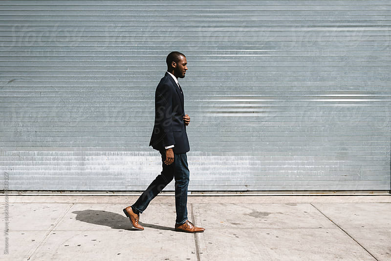 Black businessman walking in the street by Simone Becchetti for Stocksy United