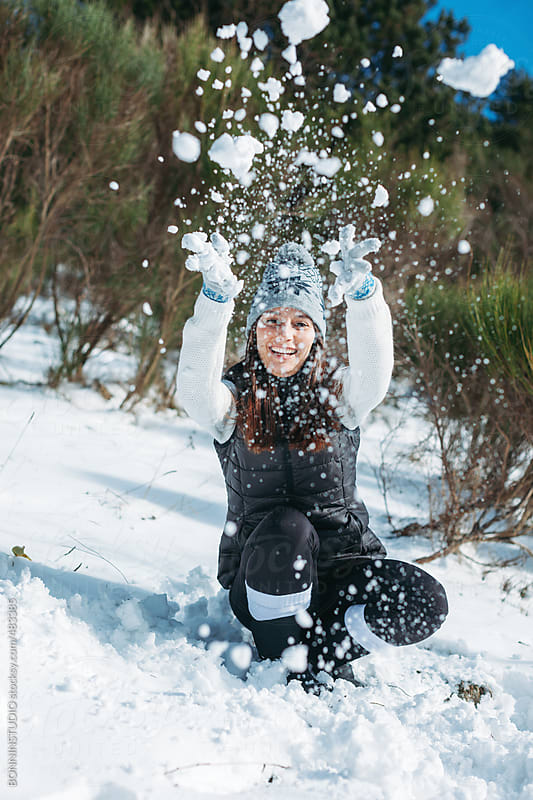Young woman having fun on a snowy winter day at the mountain. by BONNINSTUDIO for Stocksy United