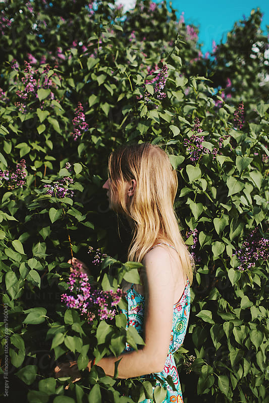Beautiful young blonde woman standing in a flowering spring garden by Sergey Filimonov for Stocksy United