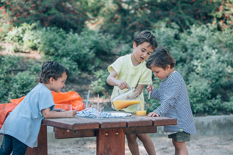 Children sharing a orange juice at the park by Lydia Cazorla for Stocksy United