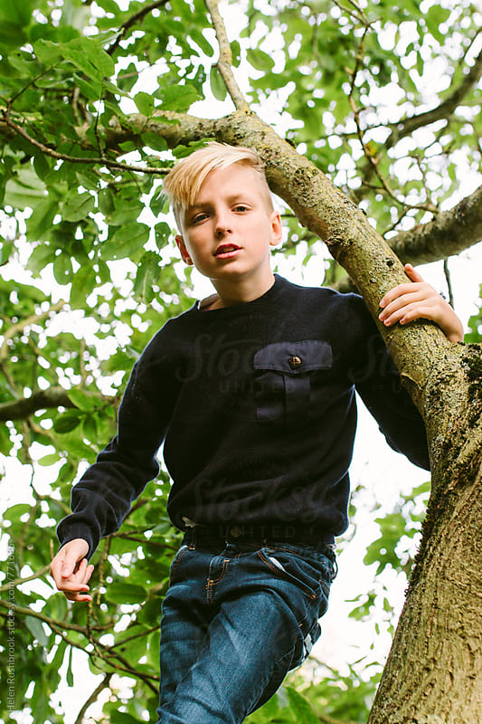 Teenage boy in a tree by Helen Rushbrook for Stocksy United