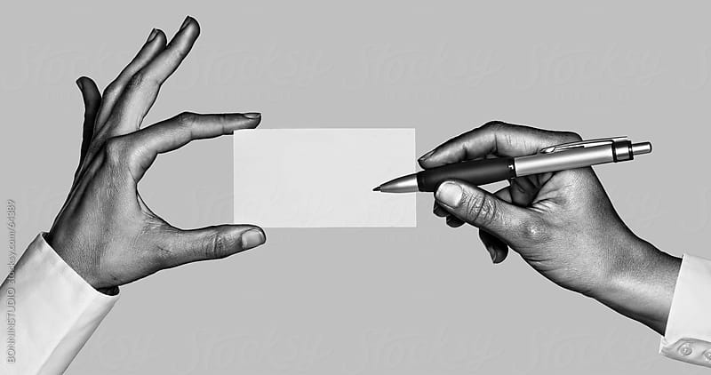 Business hands writing on business blast. Black and white photo. by BONNINSTUDIO for Stocksy United