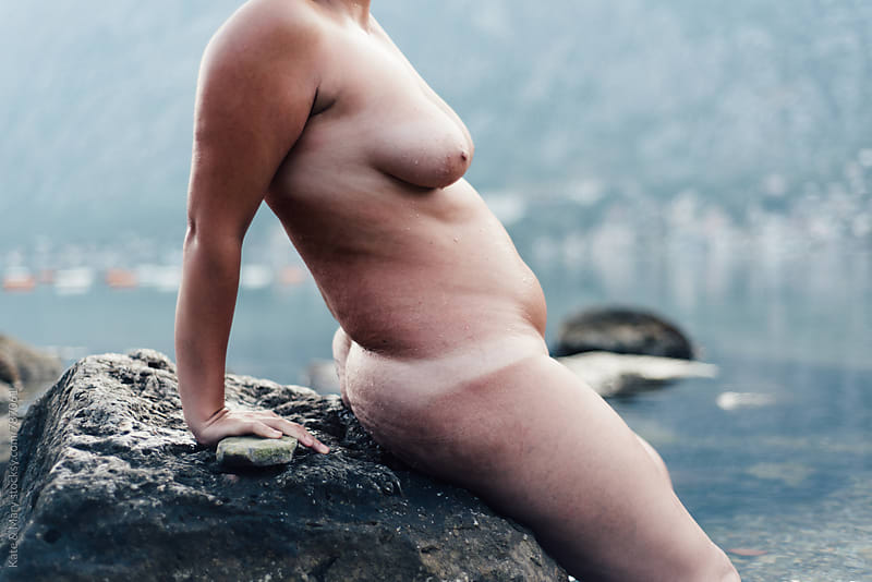 Young naked woman sitting on rock by Katarina Simovic for Stocksy United