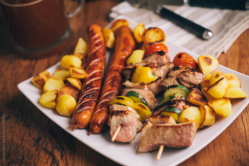 Skewers and grilled sausage with potatoes. by Davide Illini for Stocksy United