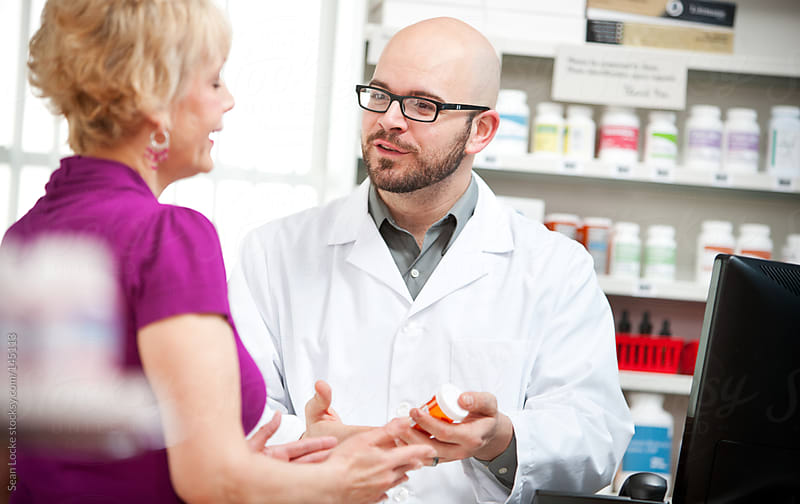Pharmacy: Cheerful Pharmacist Describing Medicine Rules by Sean Locke for Stocksy United
