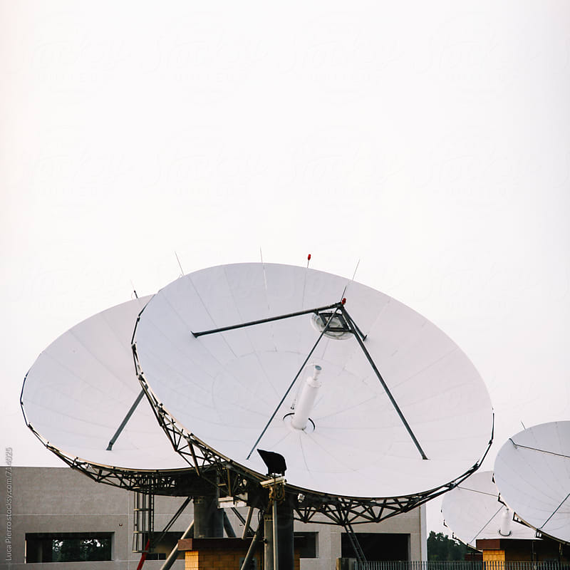 Satellite dish antennas under sky by Luca Pierro for Stocksy United