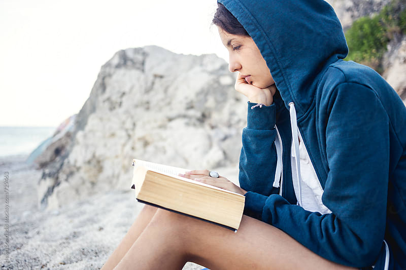 Close Up of a Young Woman Reading on the Beach by Helen Sotiriadis for Stocksy United