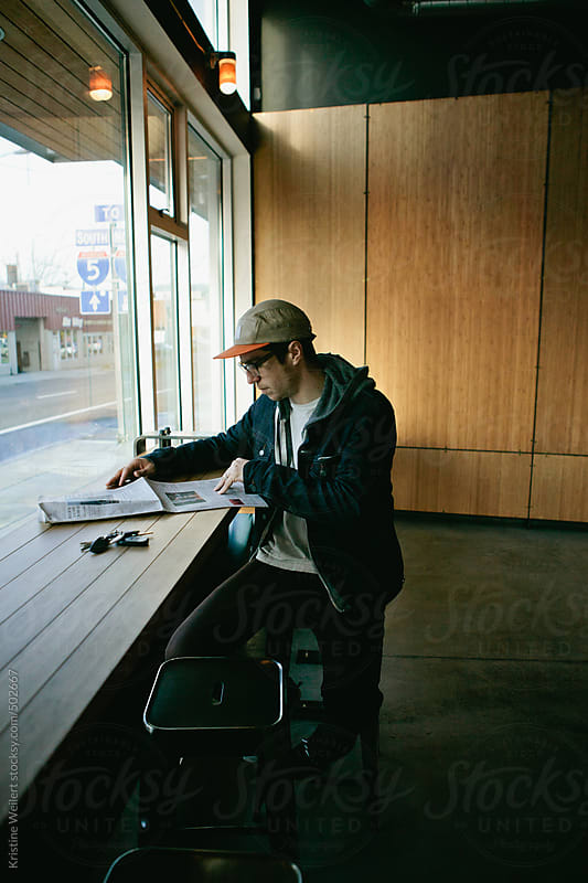 Young Man Reading a Newspaper at a Coffee Shop by Kristine Weilert for Stocksy United