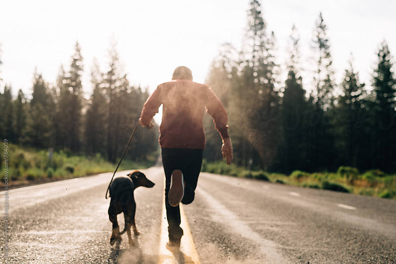 Man and dog running in road by Isaiah & Taylor Photography for Stocksy United