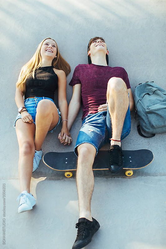 Smiling teenage couple having fun on a skate park. by BONNINSTUDIO for Stocksy United