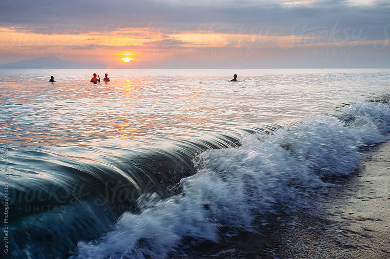Men bathing in the sea at sunrise by Gary Radler Photography for Stocksy United
