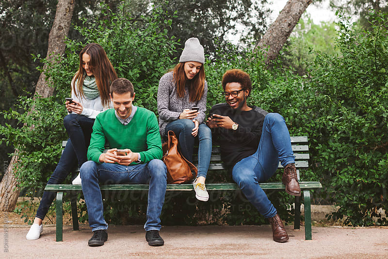 Group of friends hanging out chatting with their smartphones.  by BONNINSTUDIO for Stocksy United
