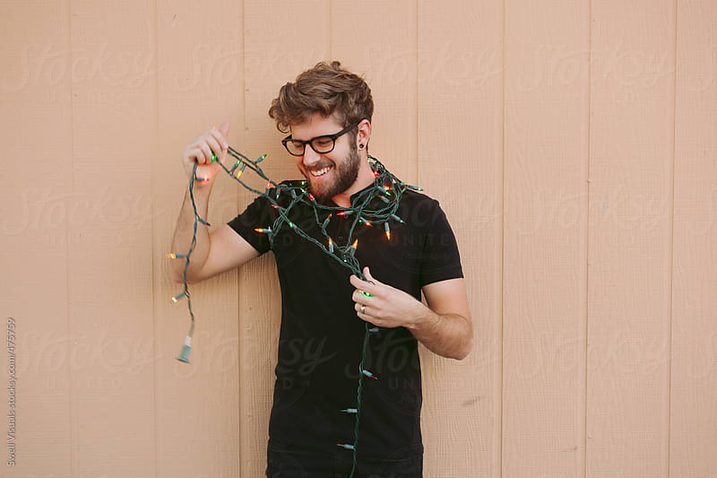 Young Man Hanging Christmas Lights by Caleb Thal for Stocksy United
