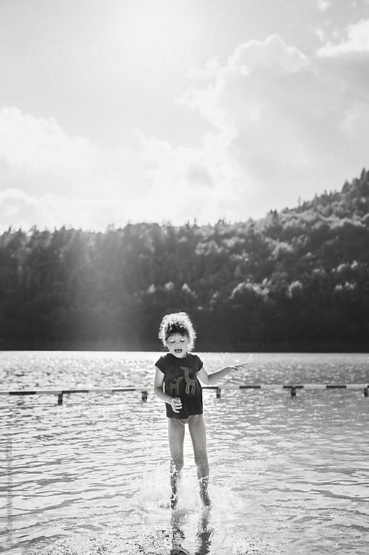 Black and white portrait of a girl jumping in a lake with her eyes closed. by Lea Csontos for Stocksy United