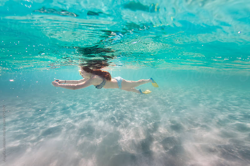 Teenage girl taking photos with a little camera under water in  the clear water of the Ningaloo Coast in Western Australia by Angela Lumsden for Stocksy United