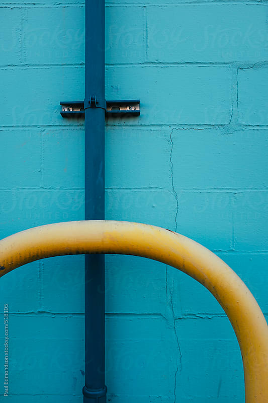 Curving yellow pipe against blue wall by Paul Edmondson for Stocksy United