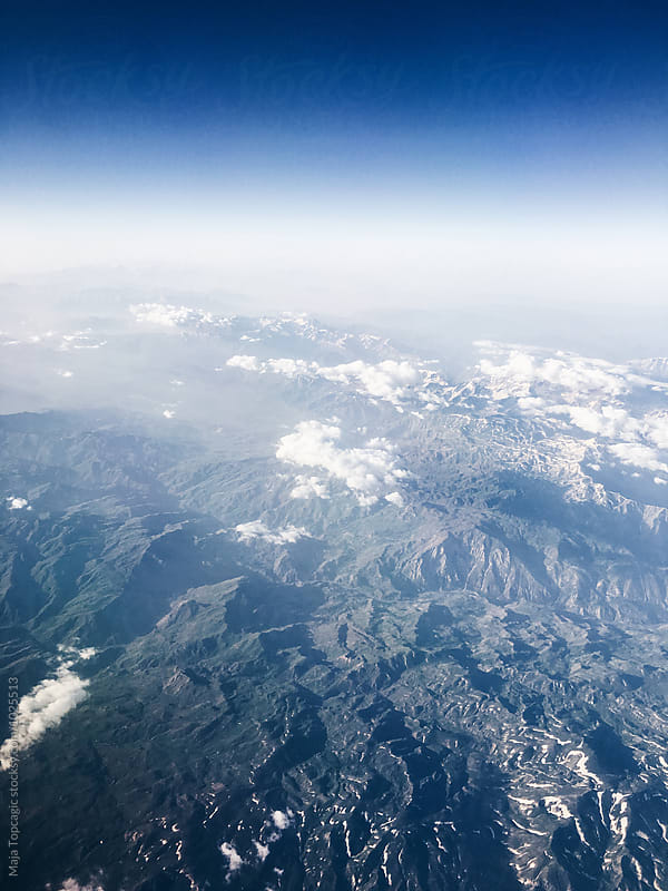 Aeroplane shot of mountains and clouds by Maja Topcagic for Stocksy United