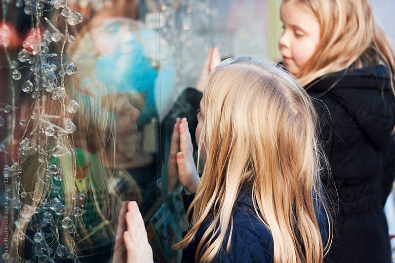 Two little girls excitedly looking at the Christmas display in a shop window. by Helen Rushbrook for Stocksy United